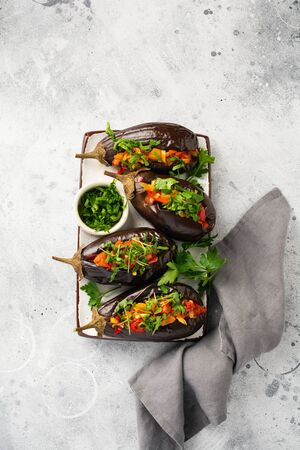 Baked stuffed eggplant with different vegetables, tomato, pepper, onion and parsley on gray stone or concrete table background. Top view.