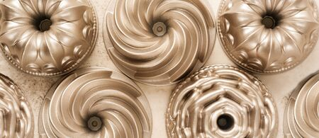 A lot of gold metal molds for baking muffins on a light brown concrete background. Banner. Top view.