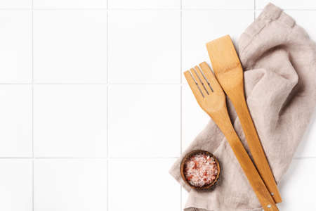 Cooking wooden utensils and cotton kitchen napkin or towel over on white kitchen wall table. Food cooking template concept. Copy space background.