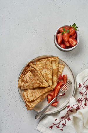 Homemade crepes with fresh strawberry on white ceramic plate on light stone background. Top view.