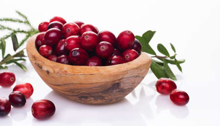 Fresh raw organic cranberry in wooden bowl plate on white background with berries next to it. Space for text.