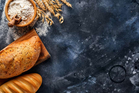 Various crispy breads and buns, wheat flour and ears on gray old concrete background table. Top view flat lay with copy space