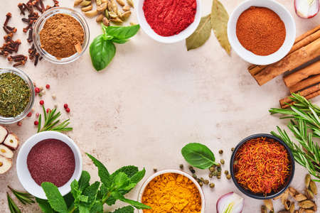 Colorful herbs and spices for cooking: turmeric, dill, paprika, cinnamon, saffron, basil and rosemary. Indian spices. On light brown stone background. Top view.