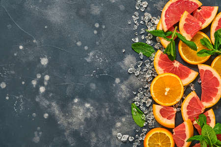 Grapefruit and orange slices, mint, cane sugar, ice, cocktail tubes, juicer or squeezer on black stone old background. Ingredients for making summer beach cocktail drink background. Mock up. Top view.