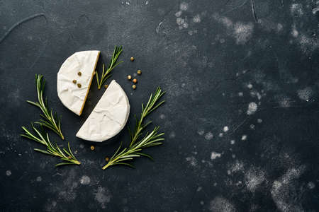 Pieces camembert cheese with rosemary, capers and pepper. On black old background. Top view. Free space for your text. Standard-Bild