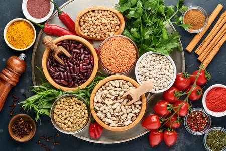 Legumes, lentils, chickpea, beans assortment, tasty appetizing ingredients spices grocery for cooking healthy kitchen on black table. Weight loss diet and fight against cholesterol concept. Top view.