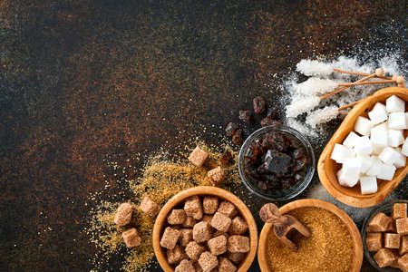 White sugar, cane sugar cubes, caramel in bamboo bowl on dark brown table concrete background. Assorted different types of sugar. Top view or flat lay.