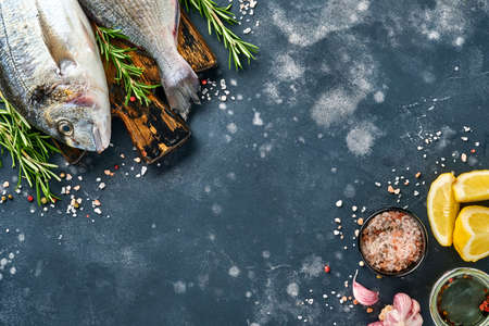 Raw dorado fresh fish or sea bream with ingredients for making lemon, thyme, garlic, cherry tomato and salt on a black slate, stone or concrete background. Top view with copy space.