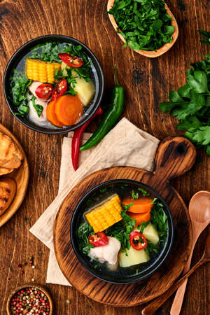Chilean meat soup with pampkin, corn, fresh coriander and potatoes on old wooden table background. Cazuela. Latinamerican food. Reklamní fotografie