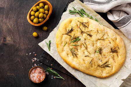 Italian traditional focaccia bread baking with aromatic seasonings and rosemary on old wooden rustic table background. Top view