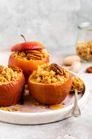 Baked Apples Stuffed with pecans, cinnamon, streyzel and honey on old concrete light background. Rustic stale Foto de archivo