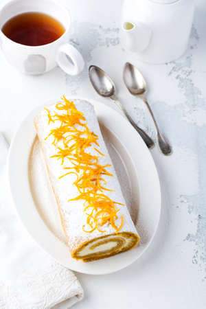 Dessert pumpkin roll with butter cream and orange server for the festive table on light gray background. Selective focus