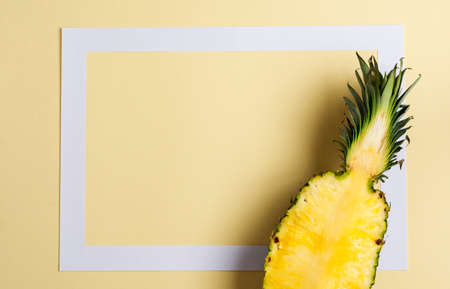 Fresh pineapple cut in two part and paper frame on yellow background. Summer concept. Creative flat lay with copy space. Top view