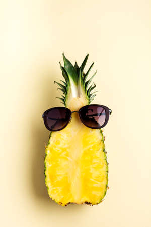 Fresh pineapple cut in two part, notebook or sketchbook and sunglasses on yellow background. Summer concept. Creative flat lay with copy space. Top view Foto de archivo