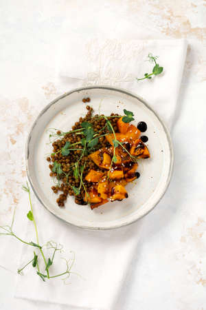 Salad with baked pumpkin, lentils and balsamic dressing garnished with peas microgreens on a light background. Healthy vegan food, top view