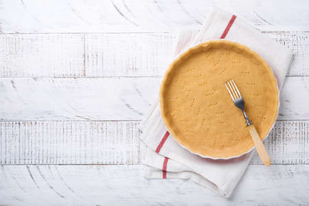 Dough for baking quiche, tart or pie in ceramic baking form ready for bake on kitchen towel over white old rustic plank wooden background. Top view, copy space. Concept homemade baking for holiday.
