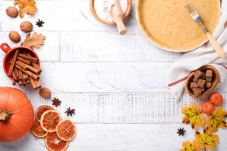 Pumpkin and food ingredients, spices, cinnamon and kitchen utencil on white rustic wooden background. Concept homemade baking for holiday. Cooking pumpkin pie and cookies for Thanksgiving day.