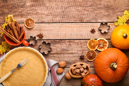 Pumpkin and food ingredients, spices, cinnamon and kitchen utencil on old rustic wooden background. Concept homemade baking for holiday. Cooking pumpkin pie and cookies for Thanksgiving day.