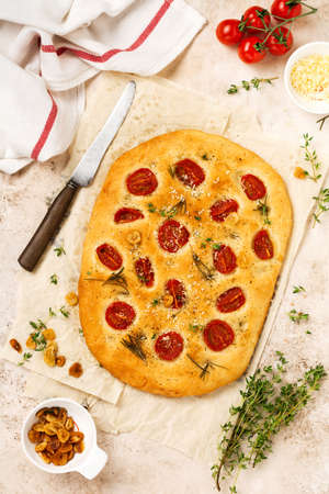 Italian traditional focaccia bread baking with with cherry tomatoes, parmesan and rosemary on light brown background. Top view