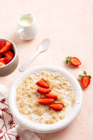 Oatmeal porridge with strawberries in a white plate on a linen napkin on pink background. Breakfast health food concept. Top view