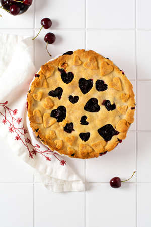Homemade open cherry pie with lattice on a gray concrete background. Selective focus. Top view