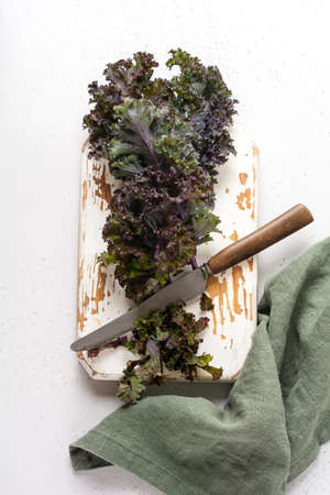 Kale leaves fresh green curly on a cutting board on a light gray slate, stone or concrete background. Selective focus. Healthy vegetarian food. Foto de archivo