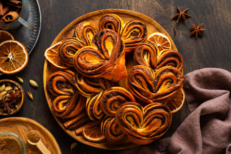 Sweet homemade cinnamon rolls in the shape of a heart on an old retro style. New Year mood. Traditional Swedish cinnabons. Selective focus