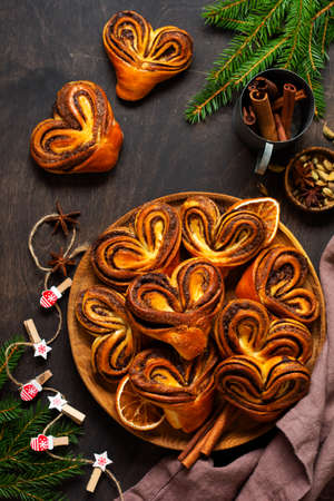 Sweet homemade cinnamon rolls in the shape of a heart on an old retro chair. New Year mood. Traditional Swedish cinnabons. Selective focus Foto de archivo