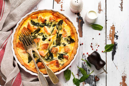 Homemade quiche tart with red fish and spinach on light wooden background. Vintage style. Top view