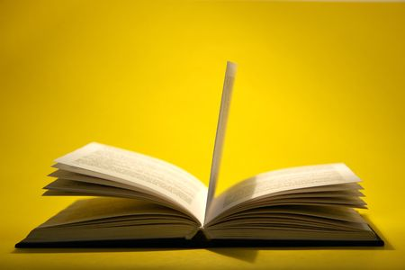 Open book with pages on yellow background Stock Photo