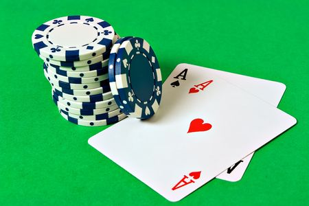 hold em: Pocket Aces and poker chips on a game table Stock Photo