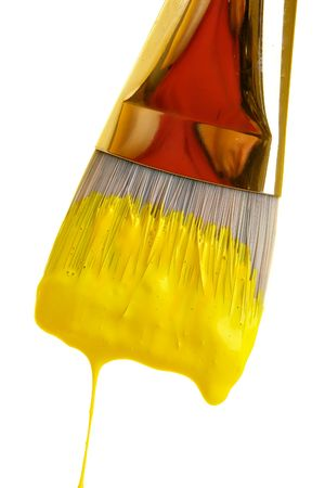 Yellow paint dripping from brush Stock Photo