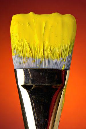 Wet yellow paint on brush