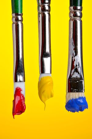 Three brushes with primary colors
