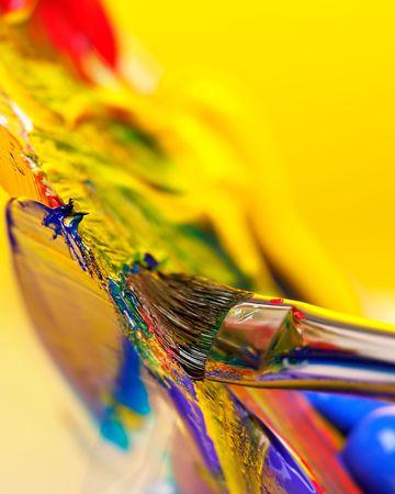 creative artist: Brush mixing paint on palette Stock Photo