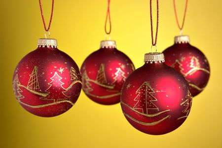 Christmas baubles hanging over yellow background Stock Photo