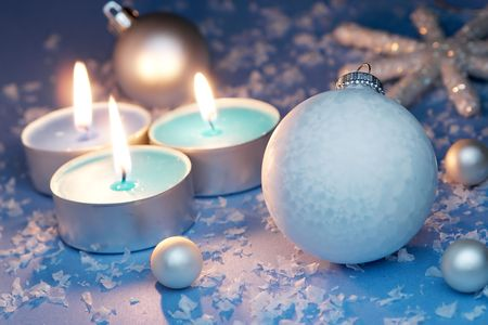 Burning candles, ornaments, blue setting
