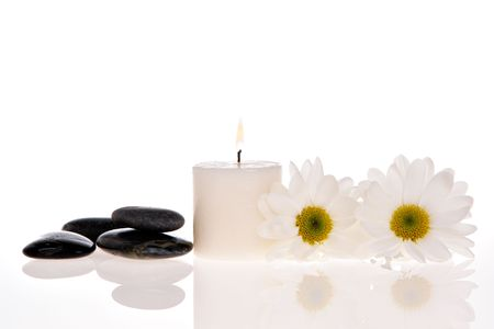 Candle, stone, and daisies isolated