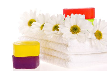 Towels, soap bars, and daisies on white isolated