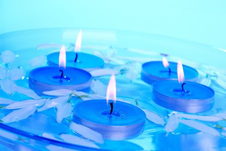 Candles and petals floating in a glass bowl