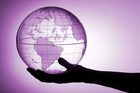 A hand holding translucent globe photo