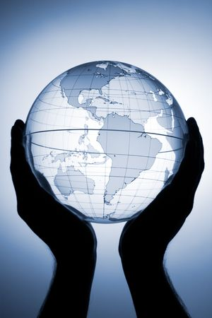 Hand holding translucent globe with blue background Stock Photo