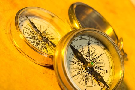 Three old style gold compasses on yellow paper Imagens - 2610533