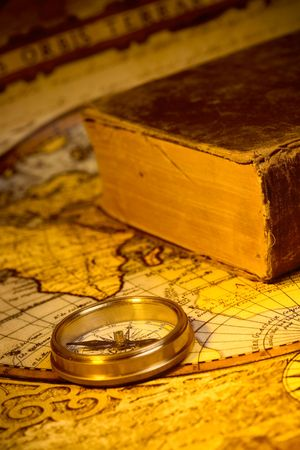 Old style gold compass and book on antique world map
