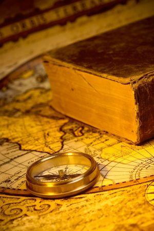 Oude stijl Gouden Kompas en boek op antieke wereld kaart Stockfoto