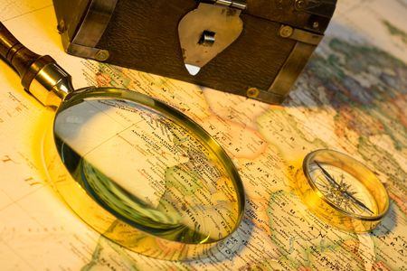 Magnifying glass, chest, compass, and map with antique look Фото со стока