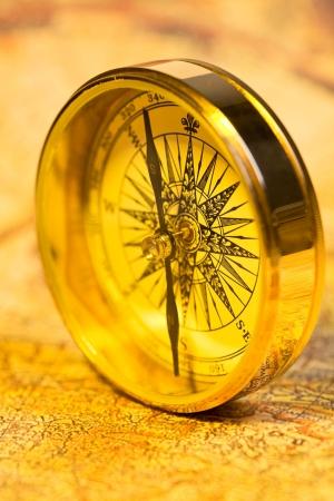 アンティーク世界地図上の古いスタイルの金コンパス