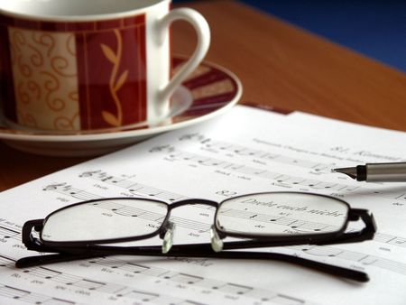 songbook: Place of employment of a music teacher. Glasses on the songbook and cup of coffee in the background.  Stock Photo