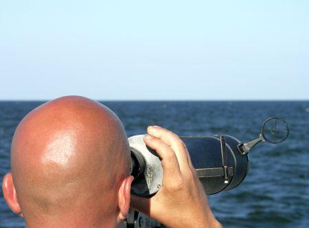 Bald man looking through binoculars, on the sea.