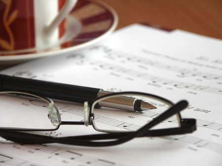 Place of employment of a music teacher. Glasses on  songbook and cup of coffee. Stock Photo
